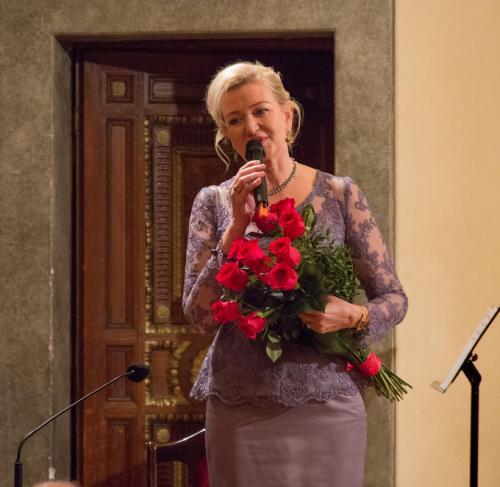 Elżbieta Gładysz obdarowana kwiatami wita publiczność.